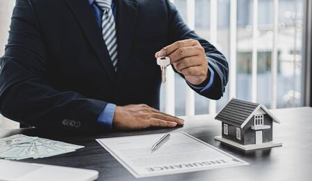 Sales manager or real estate agent prepares to hand over the keys and the house together with the insurance to the customer, Attention to property services and insurance concept. Imagens