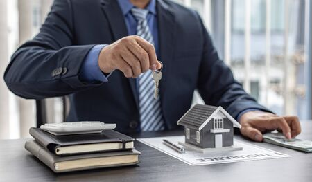 Sales manager or real estate agent prepares to hand over the keys and the house together with the insurance to the customer, Attention to property services and insurance concept.