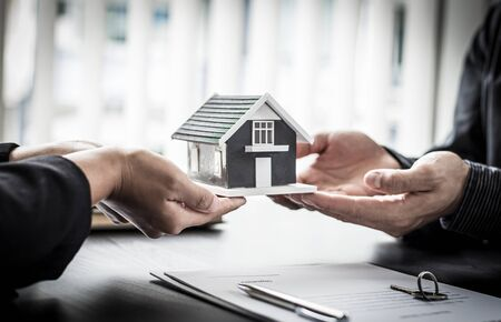 Real estate agent or sales manager has offered home sales and explained the terms of signing the house purchase contract and free home insurance, Finance and after-sales service concept.