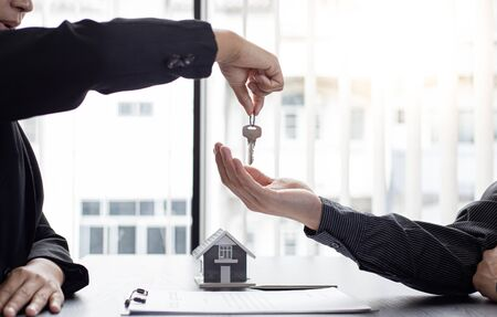 Sales manager or real estate agent holds the key handing it to the customer after signing the house purchase contract with home insurance, Trading of mortgages and insurance concept.