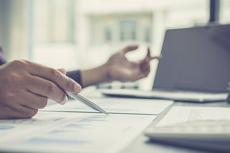 Independent financial businessmen calculate the client's annual income and analyze the market in-depth with office graphs, Income Tax Management and Financial Accounting concept.