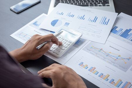 Accounting businessmen are calculating company income tax with calculators and graphs on the desks, Financial and banking profit analysis concept.