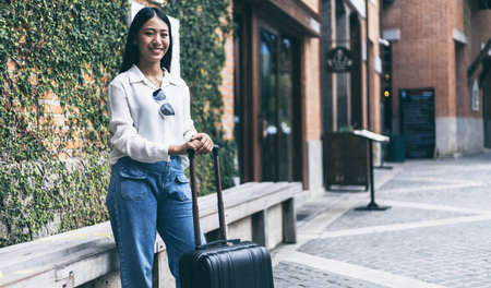 Asian woman carried a suitcase and hurried to her accommodation before her friend's appointment, Trolley bag, Long weekend travel, Love the trip, Tourism festival concept.
