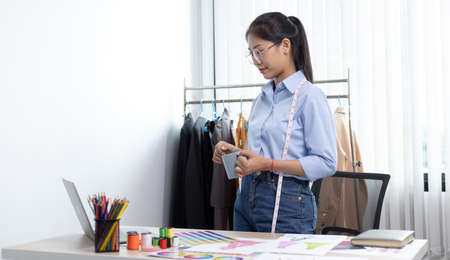 Fashion designers are working in workshops with laptops and design drawings on their desks, Creating a new collection of clothes, Creation of the work of the designer.