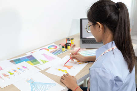 Asian clothing designers are measuring customers' body sizes in preparation for tailoring in design rooms, Creating a new collection of clothes, Creation of the work of the designer. 免版税图像