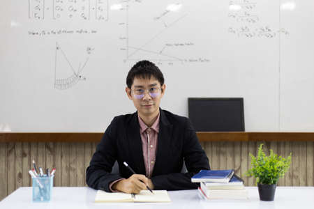 Teacher is teaching physics to students during the new school days after a long break, High school student classroom, Teacher is writing the instructional formula and explains how to do the exercises.
