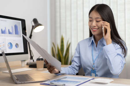 Asian female employee talking on the phone and working in a laptop with a smiling face, Office staff work and telephone conversations.