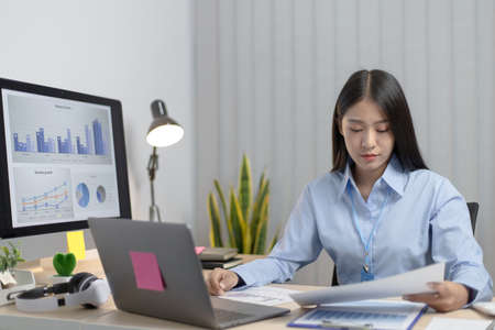 Chief marketing officer in Asia is analyzing the company's financial growth graph using personal computers for work, Working at home concept.