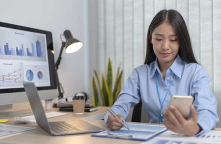 Asian female employees are analyzing market data via smartphones and have laptops to calculate the company's finances In a private office at home, Working at home and new normal concept.