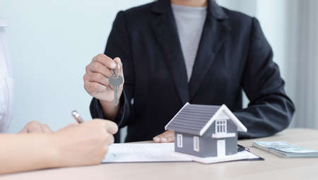 Real estate agent holds the keys to send to the client and offers the conditions for signing the house sale agreement and home insurance to the client, Home sales and home insurance concept.