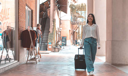 Asian woman beaming carrying a suitcase black to travel on vacation, Trolley bag, Long weekend travel, Love the trip, Tourism festival concept. Archivio Fotografico