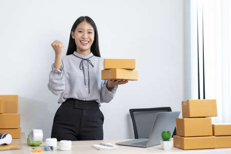 Young Asian woman chatting with a customer on a laptop and displays the product before delivery to confirm the order, Selling products online or doing freelance work at home concept.