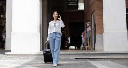 Asian woman holds a travel bag preparing to go to the accommodation and chat on the phone to a friend to meet up for a holiday party, Trolley bag, Long weekend travel, Tourism festival concept.