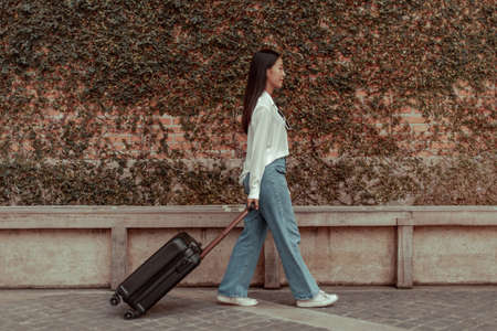 Asian woman carries a suitcase and waits for a friend to pick up on vacation, Trolley bag, Long weekend travel, Love the trip, Tourism festival concept. Archivio Fotografico