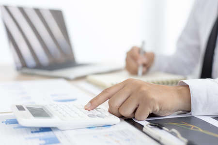 Accounting businessmen are calculating income-expenditure and analyzing real estate investment data, Dedicated to the progress and growth of the company, Financial and tax systems concept. Banque d'images