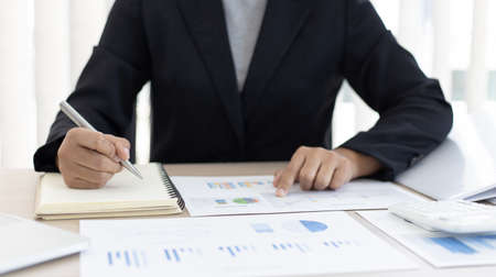 Financial businesswomen analyze the graph of the company's performance to create profits and growth, Market research reports and income statistics, Financial and Accounting concept. Stock Photo