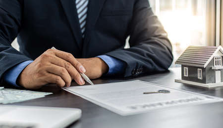 Sales manager or real estate agent prepares to hand over the keys and the house together with the insurance to the customer, Attention to property services and insurance concept. Banco de Imagens
