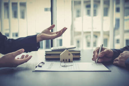 Real estate agent or sales manager has proposed terms and conditions to customers who sign house purchase agreements with insurance, Agreement to sign the purchase contract concept.