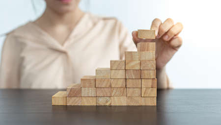 Arrange the wooden blocks into steps, higher the marketing strategy the more effort is required, Driving business at the peak concept.