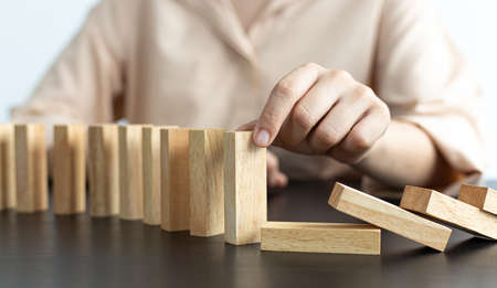 Businesswoman stops hands falling over domino to stop risk continuously, Continuous damage reduction, Stop business domino failures concept.