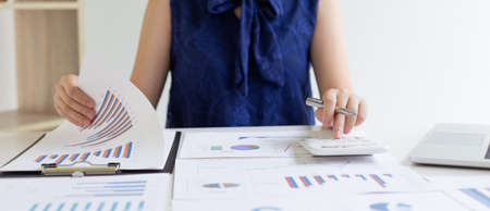 Accounting businessmen are calculating income-expenditure and analyzing real estate investment data, She works on a desk has graphs and calculators with laptop, Financial and tax systems concept.