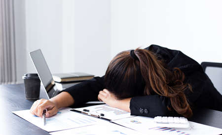 Financial accountant works on analyzing and summarizing the company's incomes and expenses in real estate and account management, causing her to get tired and fall asleep on her desk, Hard work and overtime work concept. 写真素材