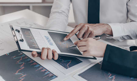Accountants and financiers are brainstorming the analysis of revenue performance with stock graphs at meetings, Analysis of real estate investment and income tax data concept.