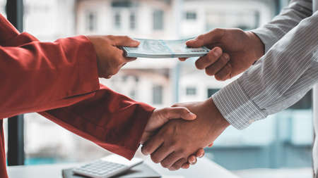 Shaking hands with congratulations on an evil plan, Businessmen give dollars to bribe employees in signing contracts to buy illegal land and real estate, corruption and Bribery concept.