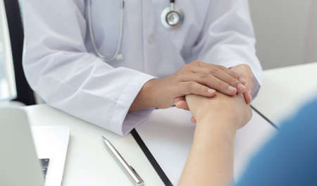 Two people shaking hands, Doctor comforted or encouraged the patient in the operating room of the hospital, Psychological behavior concept.