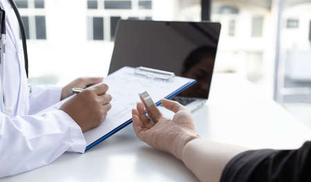 Doctor is looking at the patient's finger splint, finger straight with orthopedic device, Treatment or examination of the patient's condition.