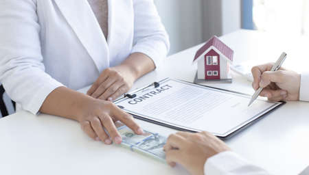 Real estate and insurance agents gave the house to customers who paid with dollar bills, Financial audit, accounting for business people concepts.