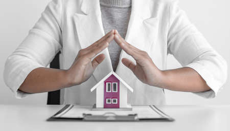 Sales manager or real estate agent prepares to hand over the house together with the insurance, Attention to property services and insurance concept.
