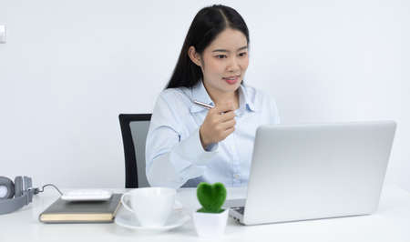 Asian woman is studying online via the internet with a cheerful smile, stay home, New normal, Covid-19 coronavirus, Social distancing, Internet learning.