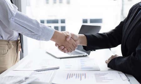 Financial accountants and marketers shaking hand to congratulate the double-digit real estate performance, Meetings and hand shake concept. Stock Photo