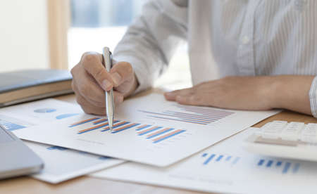 Accounting businessmen are calculating income-expenditure and analyzing real estate investment data, He works on a desk has graphs and calculators with laptop, Financial and tax systems concept.