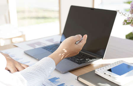 Vigorous businessman analyzes the company's financial performance in a private office, Calculation of financial accounting income and presentation for work. 免版税图像