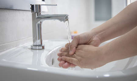 Men are washing their hands in the sinks to clear respiratory bacteria and viruses, sanitation and reduce the spread of virus that is spread around the world, Hygiene ,Sanitation concept. Banque d'images