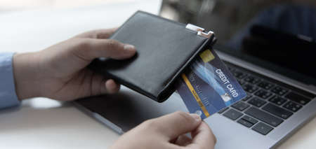 Young Asian man is taking a credit card from a black leather wallet to pay, Spending without carrying cash or payment, Online shopping concept.