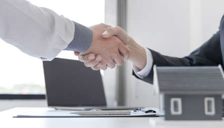 Real estate agents and customers shake hands to congratulate on signing a contract to buy a house with land and insurance, handshake and Good response concept. Standard-Bild