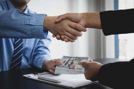Businessman shaking hands with money in hand – bribe, Two young men held hands and agreed to plot a corrupt or illegal act, Combating wrongdoing or stopping corruption.