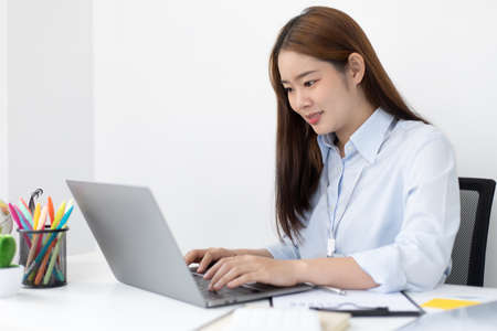 Young Asian office worker presses her finger on a laptop keyboard to analyze financial data and summarize her work in a private office, Office workers, beautiful female employee wearing a blue shirt.