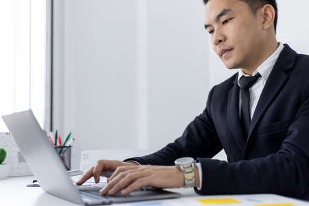 Young Asian office worker presses he finger on a laptop keyboard to analyze financial data and summarize her work in a private office, Office workers, handsome male employee in a black suit.