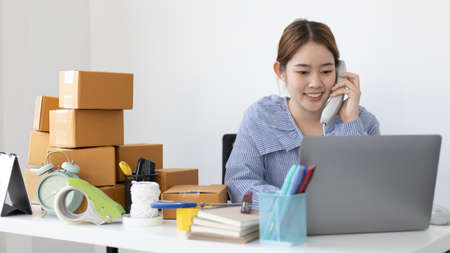 Asian businesswoman is taking online orders from a phone and chatting with customers to confirm their order, Selling products online or doing freelance work at home concept.