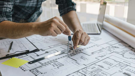 Architectural building design and construction plans with blueprints, Young man was designing a building or architecture with a ruler, pen, pencil, tape measure, architect hat and other equipment on the desk.
