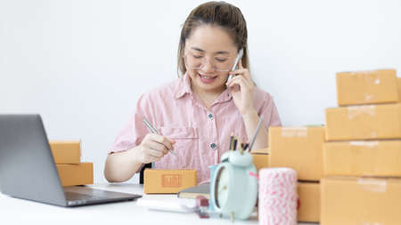 Young woman selling products online was talking on the phone to receive an order from a customer who called and wrote down the list in a notebook, New kind of business for young, Sell online. Standard-Bild