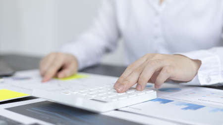 Young Asian businesswoman presses a calculator to calculate income tax and corporate income in a private office, Finance, Accounting, Tex, Statistical graphs of marketers investing in real estate.