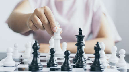 Businesswoman holding chess to take down opposing players, Proactive business planning and marketing strategy just like playing chess, Business competition and success, Leadership concept. Banco de Imagens