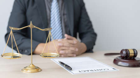 Male lawyer or judge sits and analyzes the case and decides the case with fairness, On the table were the scales of justice and the hammer of honest judgment, Concepts of Law and Legal services.