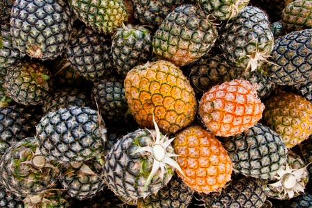 Stack of ripe many pineapples on the market as a background