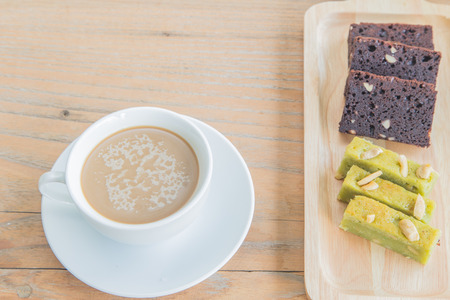 dring: Coffee with white cup and green cake on the wooden background